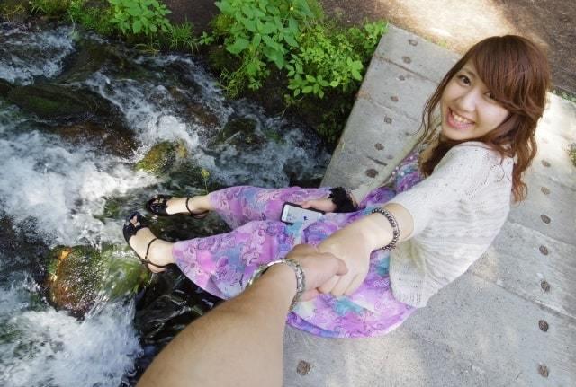 河原で座り彼の手を引く女性