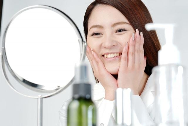 鏡に向かって笑顔の女性