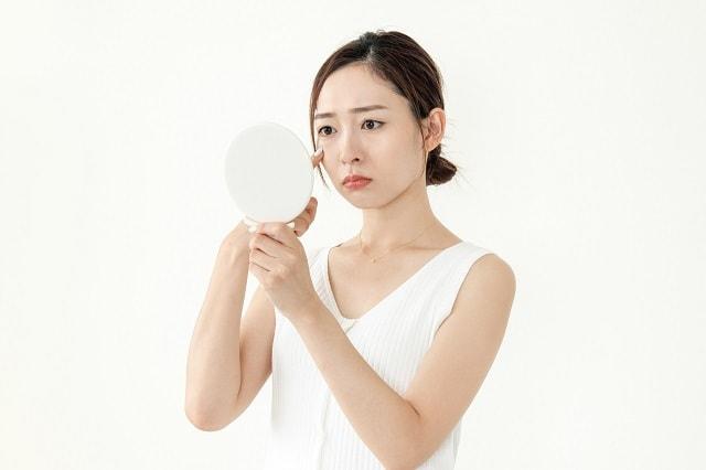 手鏡を見て顔の肌を気にする女性